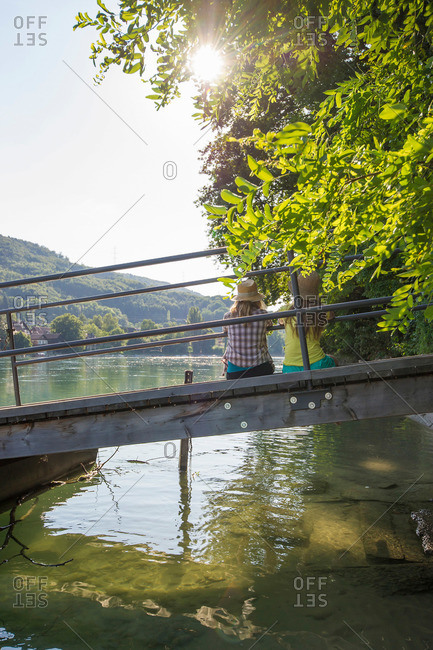 Two young women sitting on a jetty at river Rhine, Rheinfelden, Baden-Wuerttemberg, Germany