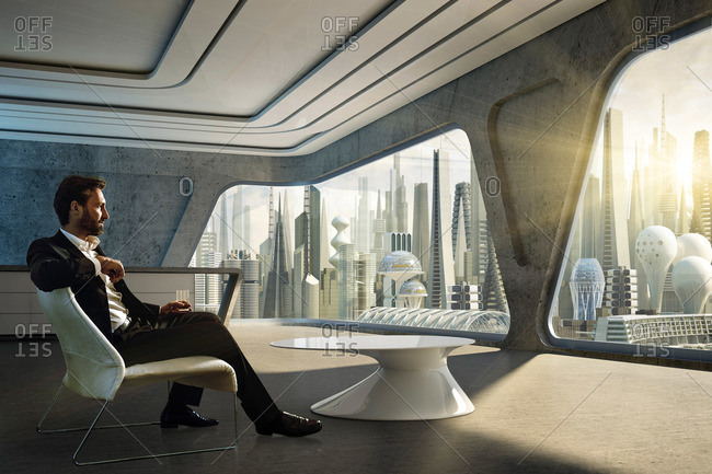 Man sitting inside a modern apartment and looking at a futuristic city skyline, Hamburg, Germany