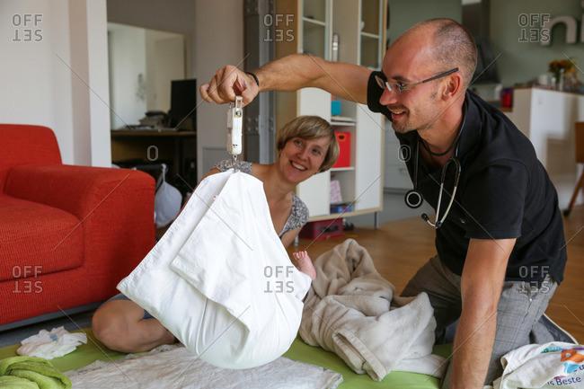 Pediatrician weighing a new born baby, Leipzig, Saxony, Germany
