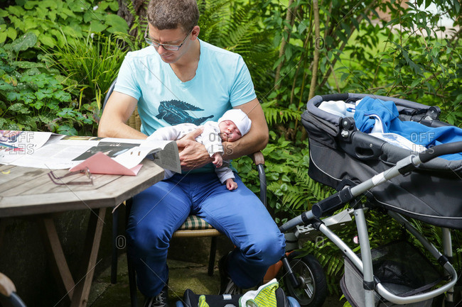Father holding new born daughter on arm while reading a newspaper, Leipzig, Saxony, Germany