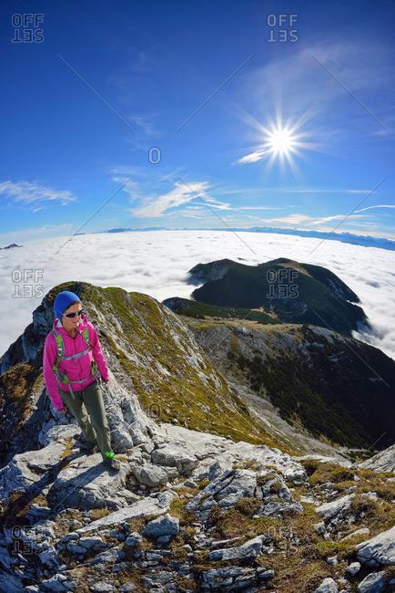 Woman ascending on ridge to Guffert, Brandenberg Alps (Rofan), Tyrol, Austria