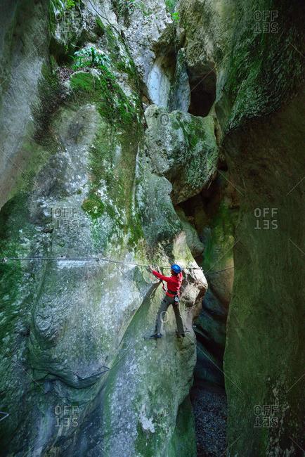Woman ascending on fixed-rope route Sentiero Rio Sallagoni through canyon of Sallagoni, Sentiero Rio Sallagoni, Garda Mountains, Trentino, Italy