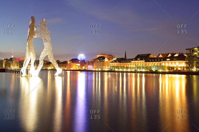 Berlin, Germany - November 3, 2013: Illuminated artwork Molecule Man above the river Spree, artist Jonathan Borofsky, Berlin, Germany