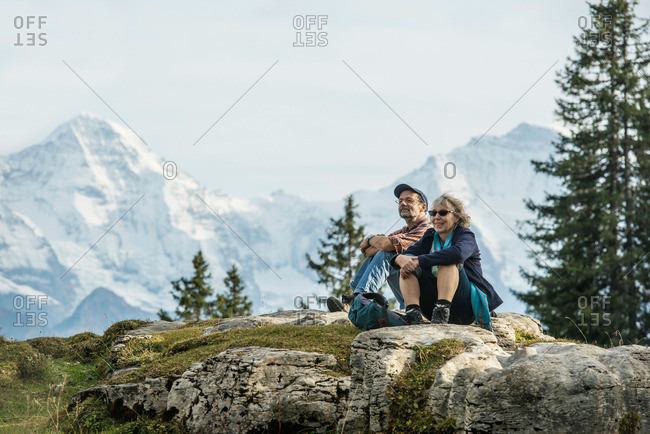 Couple resting on a rock, Eiger, Moench and Jungfrau in background, Beatenberg, Bernese Oberland, Canton of Bern, Switzerland