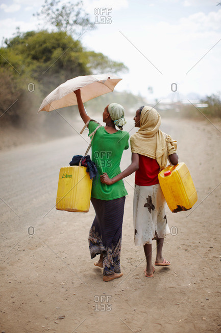Young women with cans on the way to the public water pipe, near Adi Ar Kay, Amhara region, Ethiopia