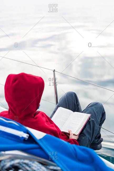 Woman reading on the deck of a sailing boat, Gulf of Trieste, Gorizia, Friuli Venezia Giulia, Italy