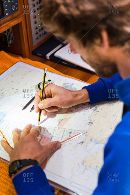 Skipper planning a route on a nautical chart at a sailing boat, Pula, Istria, Croatia