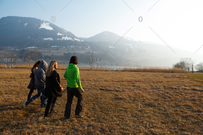 Young people crossing a meadow, Grosser Alpsee, Immenstadt, Bavaria, Germany