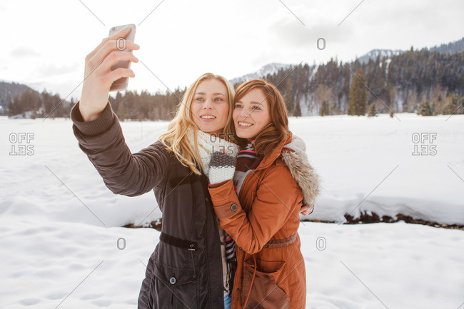 Two young women taking a selfie picture, Spitzingsee, Upper Bavaria, Germany