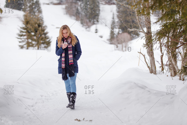 Woman using a mobile phone while walking in snow, Spitzingsee, Upper Bavaria, Germany