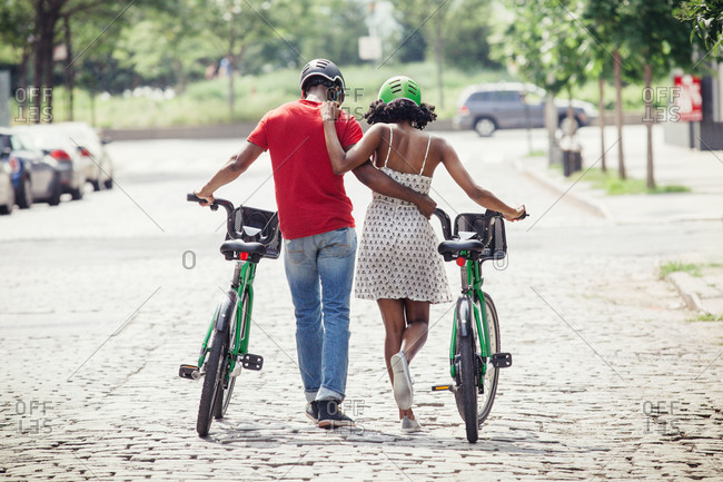 Couple walking arm in arm with their bikes