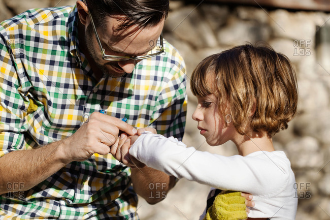 Father examining his daughter's arm