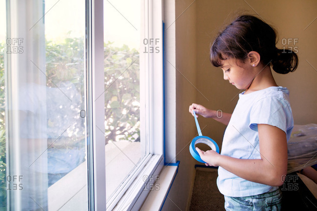 Girl with trim tape helping paint a room