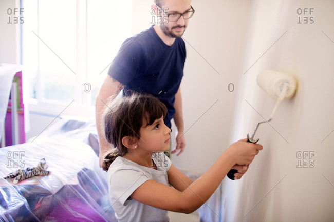 Father supervising his daughter painting