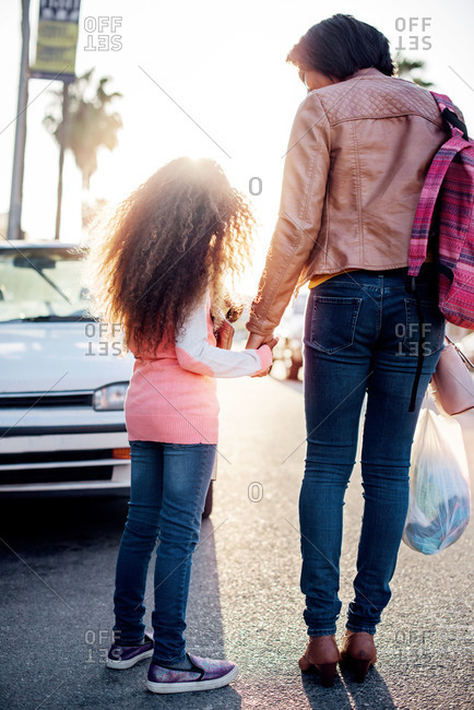 Mother and daughter holding hands on a street