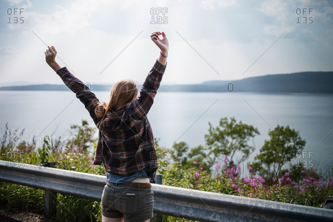 Woman stretching and looking at view over water