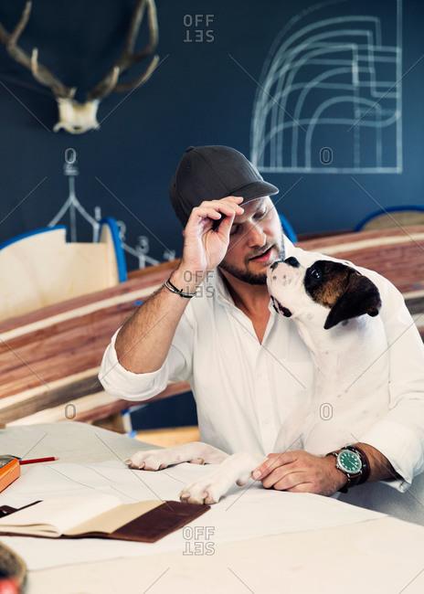 Designer's work interrupted by his dog