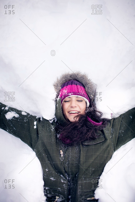 Woman having fun making snow angels