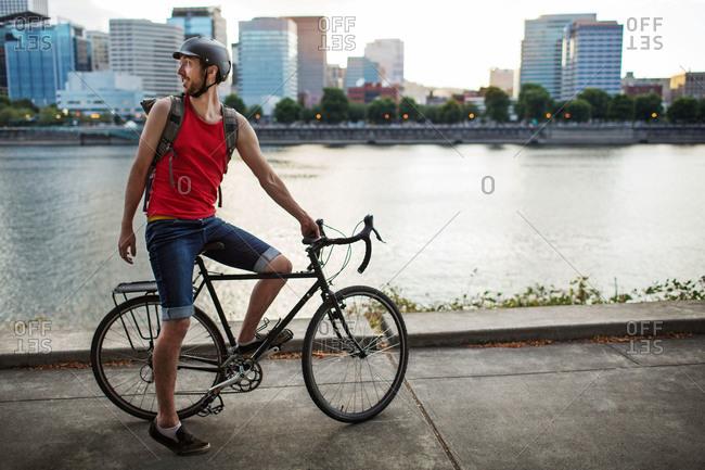 Man with a bike along an urban waterfront