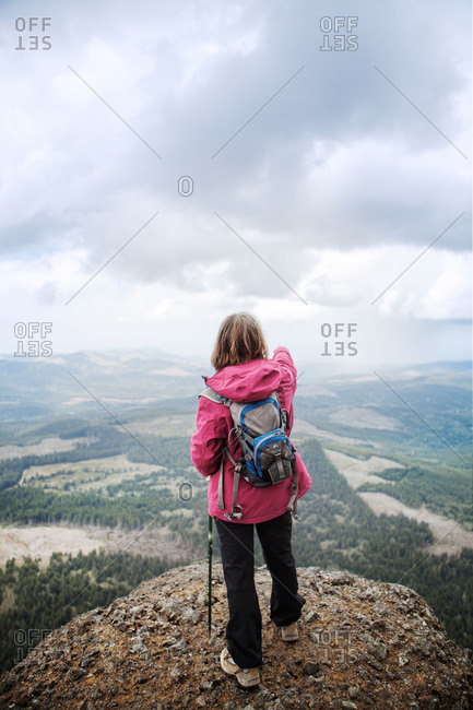 Hiker looking over landscape from mountain peak