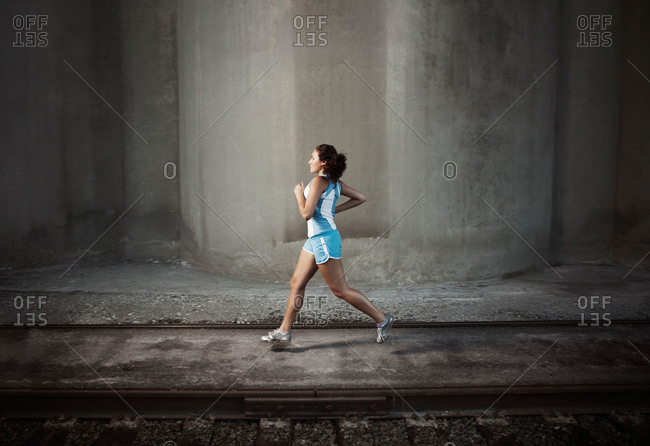 Woman running next to train tracks