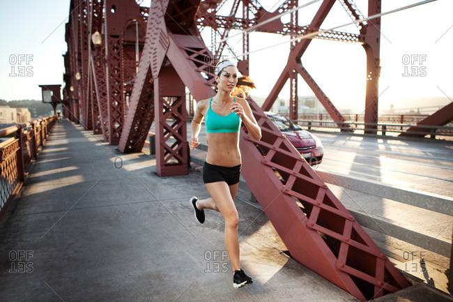 Woman jogging over a bridge