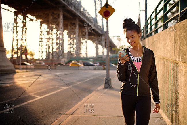 Young woman with a smartphone and ear buds