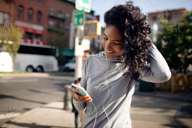 Young woman with ear buds and a smartphone