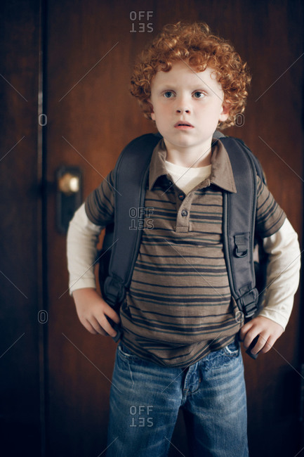 Portrait of a boy with red hair wearing a backpack