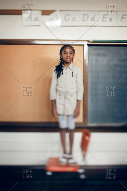 Girl standing on a chair in a classroom