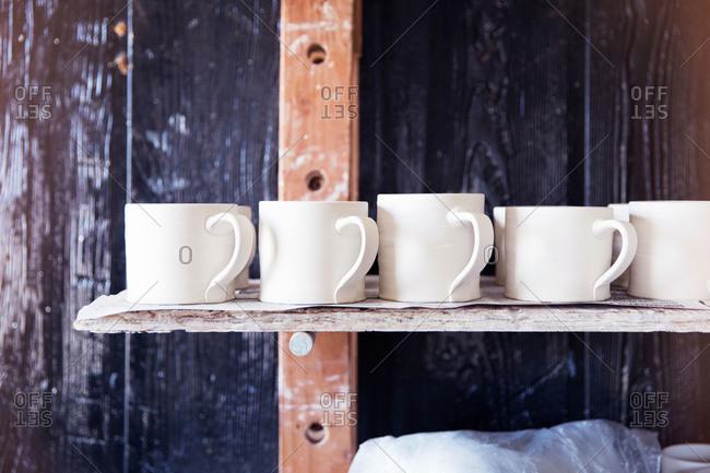 Close up of clay mugs drying on a shelf