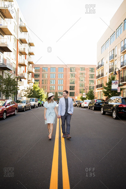 Couple walking in the middle of a city street