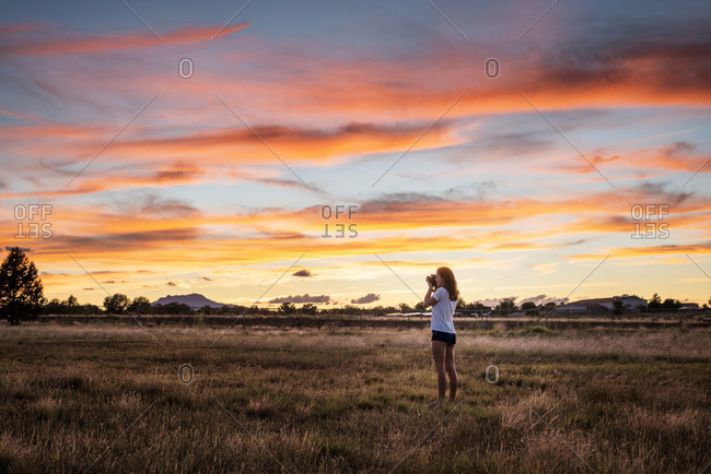 Woman in a field photographing the sunset