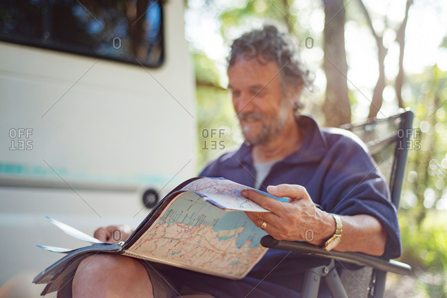 Man looking at maps outside his RV