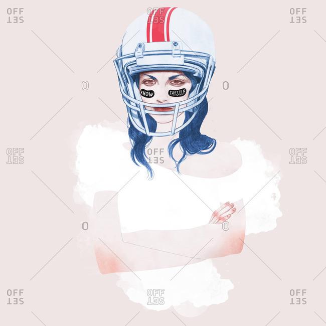 Tough young woman wearing a football helmet