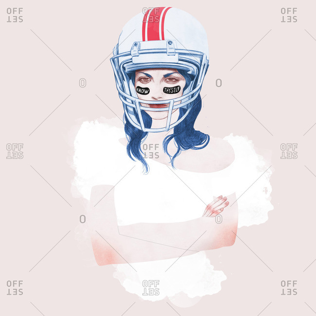 Tough young woman wearing a football helmet