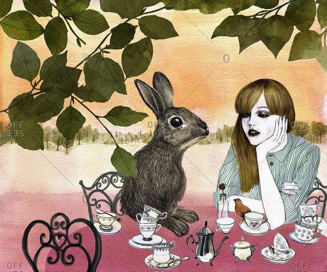 Young woman having tea with a rabbit