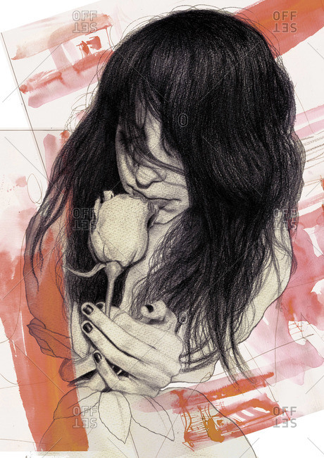 Young woman smelling a rose