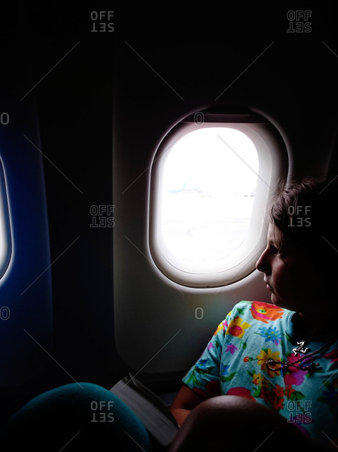 Young woman with book looking out of plane window