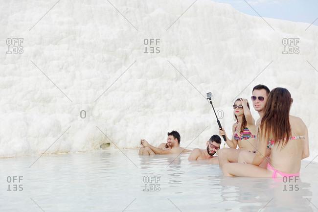 Cappadocia, Turkey - August 8, 2015: Tourists in water by travertine wall in Pamukkale, Turkey