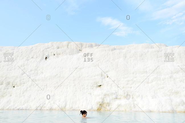 Cappadocia, Turkey - August 8, 2015: Woman swimming by travertine wall in Pamukkale, Turkey