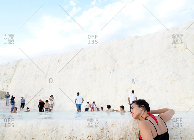 Cappadocia, Turkey - August 8, 2015: Tourists swimming by travertine wall in Pamukkale, Turkey