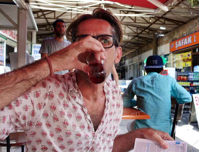 Bodrum, Turkey - August 14, 2015: Man drinking at outdoor cafe in Turkey