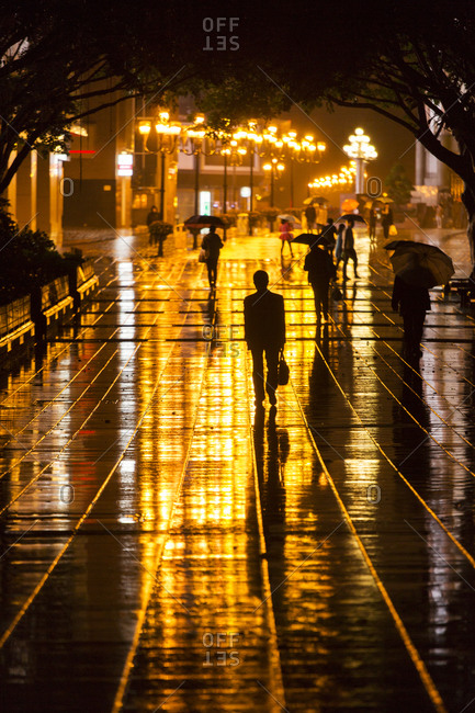 Pedestrians in rain at night, Chongqing, China