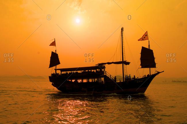 A junk sails through Aberdeen harbor near Hong Kong at sunset, Hong Kong, China