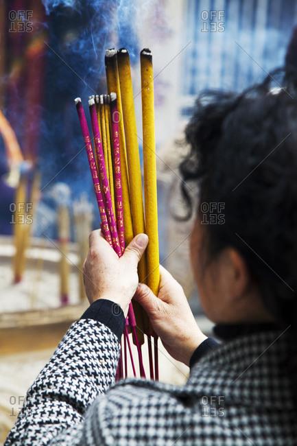 Woman burning incense and praying at A-Ma Temple, Macau, China