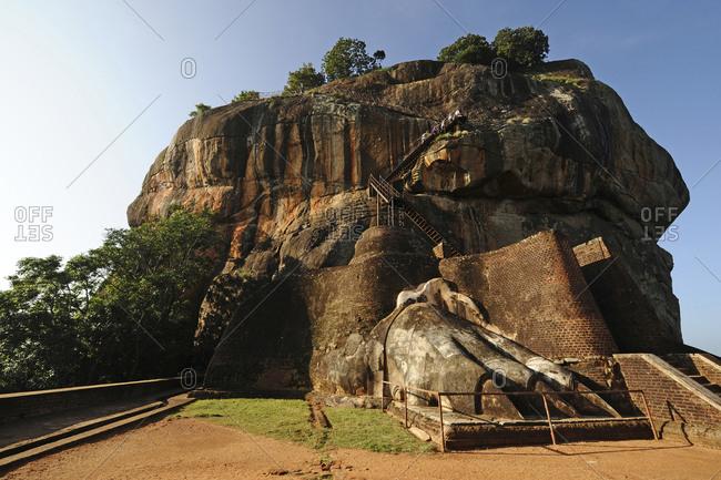 Tourists climbing the lions paw rock entrance at Sigiriya Rock Fortress, Sigiriya, Sri Lanka