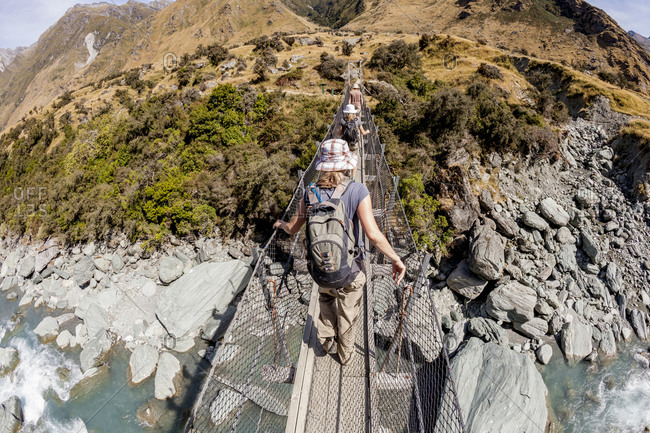 Hikers cross a footbridge over the Matukituki River on the Rob Roy Glacier Trail outside of Wanaka, New Zealand.