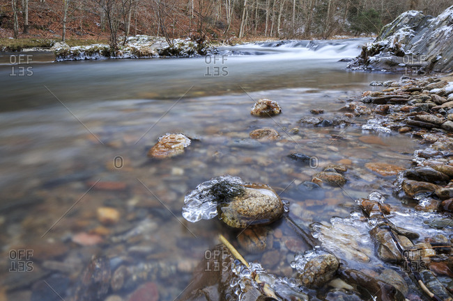 Long exposure of a mountain stream with ice in the foreground,  in North Carolina, USA