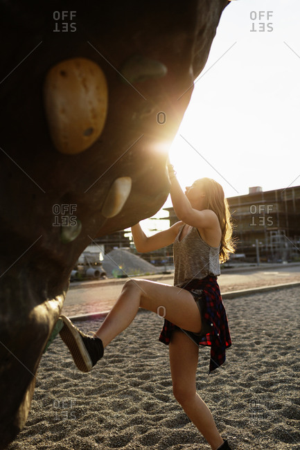 Young woman attempting to climb a rock wall at an urban park